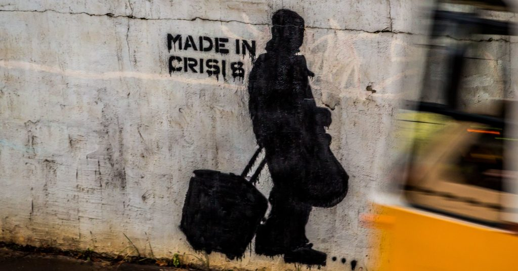 """Stencilled image of a man against a wall with a caption that says """"made in crisis"""""""