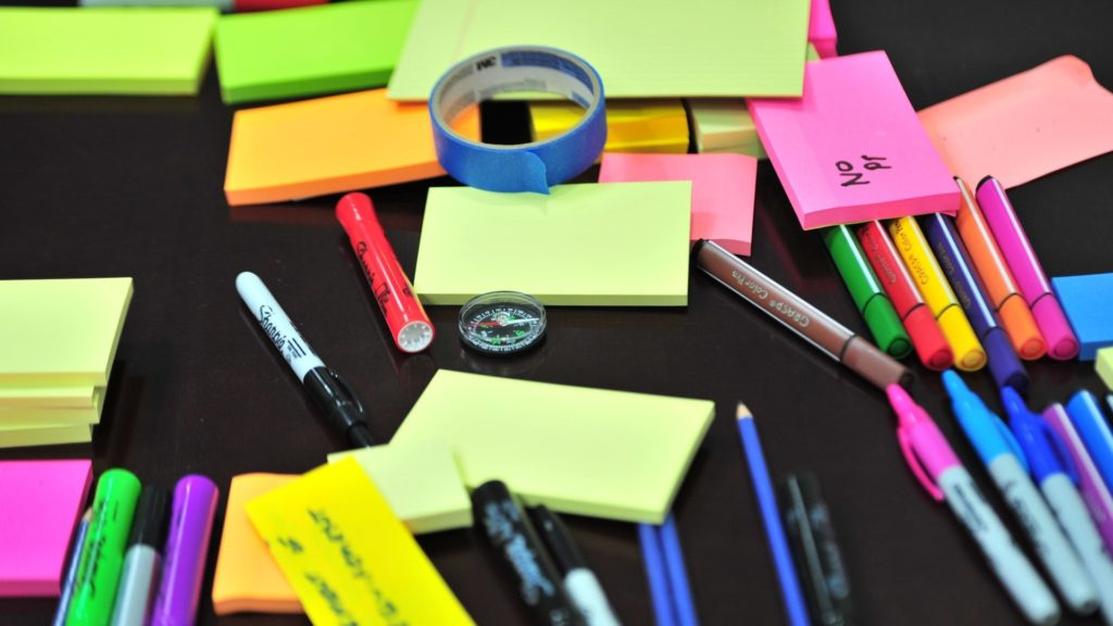 Post it notes of various colours with pens and pencils ready for a brainstorming session.